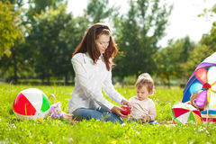 Beautiful Mom and baby outdoors. Happy family playing in nature. Royalty Free Stock Photo