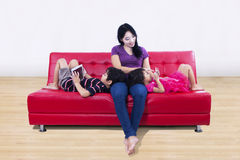 Beautiful mom and children on red sofa at home Stock Images