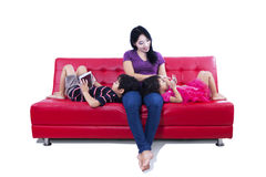 Beautiful mom and children on red sofa - isolated Royalty Free Stock Photography