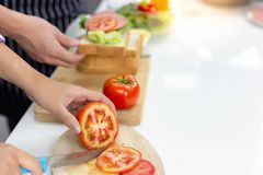 Beautiful mom is chopping tomato by using knife on cutting board stock image