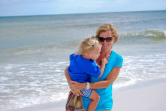 Beautiful mom and daughter on the beach. Mom and young daughter happy in the sand on the beach Stock Image