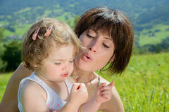 A beautiful mom and daughter play with a flower stock photo