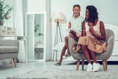 Beautiful mom discussing drawings with cute little pretty cheerful child. Having conversation with daughter. Beautiful alluring smiling Afro-American mid-adult royalty free stock photography