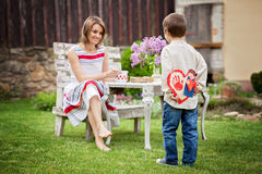 Beautiful mom, having coffee in a backyard, young cute child giv. Ing her present and flowers for her birthday. Mother day concept, love, happiness, cozy Royalty Free Stock Photography