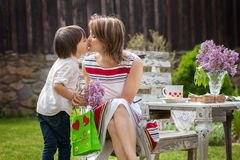 Beautiful mom, having coffee in a backyard, young cute child giv Stock Photos