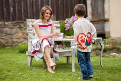 Beautiful mom, having coffee in a backyard, young cute child giv Stock Images