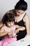 Beautiful mom helping her daughter drawing Royalty Free Stock Photos