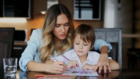 Beautiful mom helps her son to paint with colored pencils image. Helping to develop a child`s imagination.