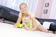 Beautiful mom with her son playing happily. Young decorative mom plays with her son Royalty Free Stock Images