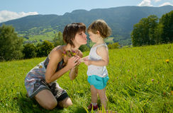 A beautiful mom is a hug to her daughter. With a flower in his garden Stock Images
