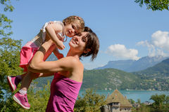 A beautiful mom is a hug to her daughter stock image