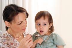 Beautiful mom ifeeding her daughter Stock Photos