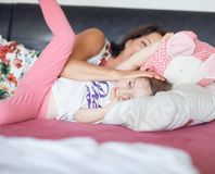 Beautiful mom lying in bed with her little daughter, having fun stock image