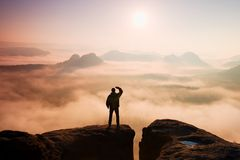 Beautiful moment the miracle of nature. Man stands on the peak of sandstone rock in national park Saxony Switzerland and watching Stock Image
