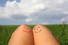Beautiful moments in two. Peace or love concept. Coceptual blue and red emoticon on girls legs. Stock Photo
