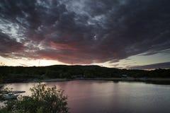 Beautiful moody sunrise over calm lake. Stunning dramatic sunrise over calm lake Royalty Free Stock Images