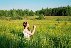 Beautiful mori girl playing the pipe. On the background of a summer field with flowers. Wreath in the hair, playing the flute royalty free stock images