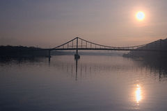 Beautiful morning cityscape. The sun is reflected in water. silhouettes of houses hidden in the haze. Pedestrian bridge to the Tru Royalty Free Stock Photography