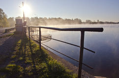 Beautiful morning lake landsacpe with fence and fog Stock Images