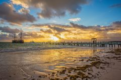 Sunrise on the Atlantic ocean. Beautiful morning landscape with caravel near wooden pier in Punta Cana. Dominican Republic Royalty Free Stock Photography