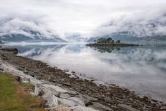Beautiful morning landscape on fjord with creeping clouds. Rocky island with trees and wonderful reflection in the water, Norway Stock Image