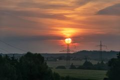 Red rising sun on top of an electric pole royalty free stock photos