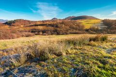 Beautiful morning scenery with hoar on the grass. Lovely autumn countryside in mountains. beautiful morning scenery with hoar on the grass and bright blue sky royalty free stock photography
