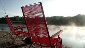 Beautiful morning scenery red chairs standing on fishing pier on background fog stock video