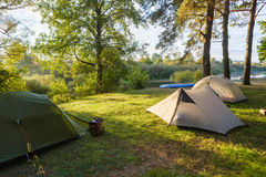 Beautiful morning sun rays illuminate tourist tents. In autumn forest royalty free stock photo