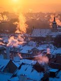Beautiful morning with sun rising over the Prague roofs covered with fresh snow. Colorful photo of the sunrise in the city royalty free stock photo