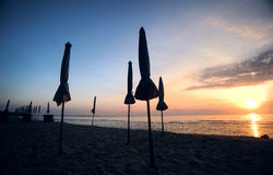 Beautiful morning sunrise with beach parasol. On the beach Royalty Free Stock Photography