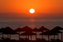Beautiful morning sunrise in Roquetas del Mar in Spain. With straw parasols on the beach Stock Photo