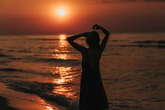 Beautiful morning sunrise, silhouette of the girl at sunset. woman relaxes by the sea. meditation concept. Beautiful morning sunrise, silhouette of the girl at stock photo