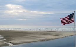 View of the Ocean and Low Tide with American Flag. A beautiful morning view of Ogunquit Beach in Maine with low tide and American flag blowing in the wind royalty free stock photo