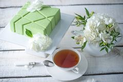 Beautiful morning wedding tea table with a square green cake on the shelf and white hydrangeas. Desserts for a festive summer mood Stock Photos