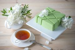 Beautiful morning wedding tea table with a square green cake on the shelf and white hydrangeas. Desserts for a festive summer mood Royalty Free Stock Image