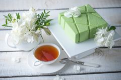 Beautiful morning wedding tea table with a square green cake on the shelf and white hydrangeas. Desserts for a festive summer mood Stock Image