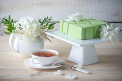 Beautiful morning wedding tea table with a square green cake on the shelf and white hydrangeas. Desserts for a festive summer mood Stock Photography