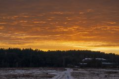 Beautiful morning and winter bright sunrise in January. Suburb and field covered snow.  royalty free stock photography