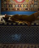 Beautiful Moroccan Girl in Short Golden Dress in Rich Mosaic interior of Picturesque Dar Si Said Riyad in Marrakech.  royalty free stock photo