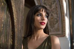 Beautiful Moroccan Girl in Short Golden Dress in Rich Mosaic interior of Picturesque Dar Si Said Riyad in Marrakech.  royalty free stock images