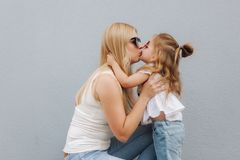 Beautiful mothe with her daughter. Blond hair female. Gray background. Best friends stock photography