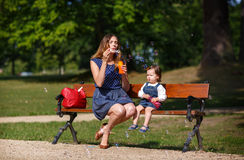 Beautiful mother and adorable daughter blowing soap bubbles in sum Stock Image