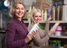 Beautiful mother and adult daughter in good spirits selecting sh. Ampoo in the store stock photography