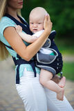 Beautiful mother with baby boy in sling walking in green park Stock Photography