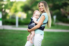 Beautiful mother with baby boy in sling walking in green park Royalty Free Stock Photos