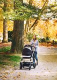 Beautiful mother with baby carriage walking in autumn park. Stock Photos