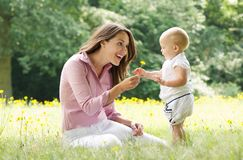 Beautiful mother with baby playing in the park Royalty Free Stock Photo