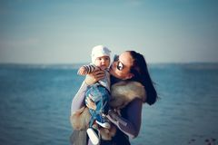 Beautiful mother with a baby resting by the blue sea stock photography