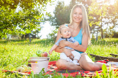 Beautiful mother with baby sitting outdoors on a blanket Stock Photo